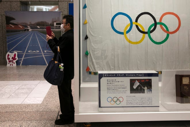 A man wearing a mask takes pictures of the mascots for the Tokyo 2020 Olympics.